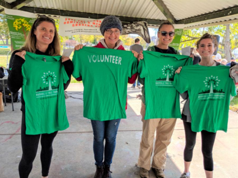Green tee volunteers holding shirts